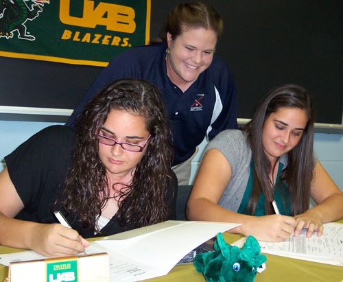 Former Gaither High School softball coach Heather Castle watched while Kristen (left) and Meagan McGrath signed to play at the University of Alabama at Birmingham last October. File photo.