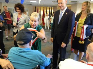 Florida's First Lady Ann Scott awards a medal to one of the residents of Baldomero Lopez State Veterans' Nursing Home in Land O' Lakes during a ceremony last week as her husband, Gov. Rick Scott, looks on. Scott has been giving his Veterans Service Award medals to veterans across the state. (Photo by Michael Hinman)