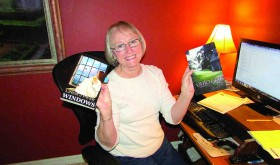 Linda Pollock, who writes under the name Linda J. Pifer, holds two of her finished works. 'Ohio Girl' is a memoir about growing up in Ohio. The other book, 'Windows,' is a novel that the author describes as part romance, part genealogical mystery. (B.C. Manion/Staff Photo)