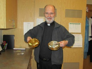 The Rev. Ron Aubin displays a silver ciborium and a gold ciborium. The silver one is used to hold the gluten-free communion hosts, and the gold one holds the traditional hosts. (B.C. Manion/Staff Photo)