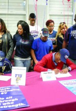 Family members surround Mark Hutchinson, left, and Jaye Miner of Wiregrass Ranch High School as they sign their letters of intent to play college football. They're the first players in the school's history to sign with NCAA Division I schools. (Michael Murillo/Staff Photo
