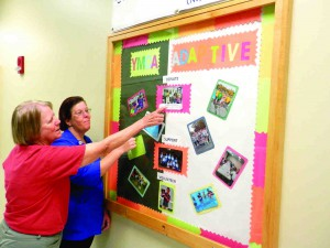 Kass Pilczuk, left, and her daughter Kathy look at the board commemorating the New Tampa Family YMCA's adaptive program. When Pilczuk first came to the facility as a swim coach 11 years ago, the program didn't exist. Now, she runs it. (Michael Murillo/Staff Photo)