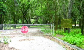 A fence, with a stop sign, blocks vehicles at the former entrance to Hercules Park. A faded sign lists park rules. (Kathy Steele/Staff Photos)