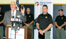 Pasco Schools Superintendent Kurt Browning holds a smartphone and talks about how easy it is for information to spin out of control during a school emergency. To counter the spread of inaccurate information, the school district and the Pasco County Sheriff's Office have set up social media sites to provide timely, factual information to parents and the public during school emergencies, Browning said. Pasco County Sheriff's Capt. James Mallo, who also took part in the news conference, is standing behind Browning. (B.C. Manion/Staff Photos)