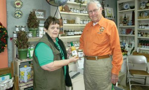 Margie Neuhofer and her husband Joseph Neuhofer are among founding growers of Kumquat Growers Inc. Neuhofer manages the gift shop. She and Frank Gude show off kumquat products sold at the shop. (Kathy Steele/Staff Photo)