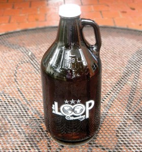 An In the Loop growler sits on a table on the patio of a former residence that is being renovated as a tap and tasting room for In the Loop Brewing.