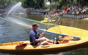 Jimmy Mason, in the foreground, of the Wesley Chapel Rotary goes after an errant rubber duck that jumped the floating lane during the Duck Derby.