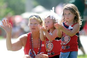 From left, Debbie Sumbury, of Lutz, and her granddaughters, 2-year-old Amelia Donovan, and 3-year-old Stella Donovan, beckon for beads along the Lutz Fourth of July parade route. Hundreds turned out for the event, despite the blazing heat. (Fred Bellet/Photo)