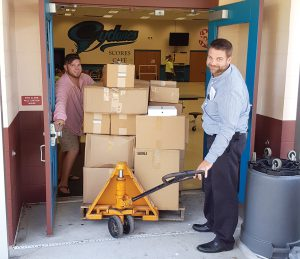 Technology teacher Dalton Smith and Assistant Principal Josh Borders are busy moving boxes — getting ready for the first day of classes at Centennial Middle School in Dade City. (Courtesy of Centennial Middle School)