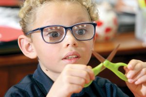Eight-year-old Will Pena prepares his scissors to begin cutting paper hearts in his classroom at Academy at the Lakes. (Fred Bellet/Photos)