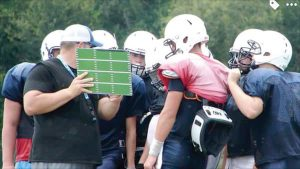 First-year head coach Anthony Egan, far left, teaches the finer points of an offensive play during a Wildcats practice. (Courtesy of Wesley Chapel High football)