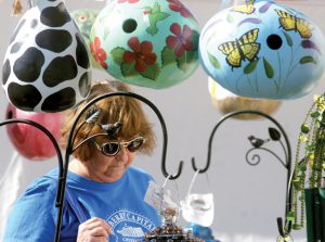 Cindy Bishop, of Tampa, browses one of the many vendor booths at the 37th annual Lutz Arts & Crafts Show, as decorative, hand-painted gourd birdhouses loom above. The festival was held at a new location, Keystone Prep High School in Odessa. (Fred Bellet/Photos)