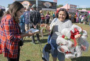 As if she did not have enough to carry, Mita Garga (right), of Lutz, holds her daughter Nena's lemonade as the two get ready to snack on a funnel cake while at the Lutz Arts & Crafts Show.
