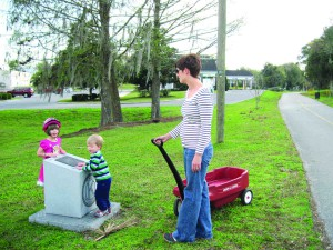 Anna Crerand takes a break from strolling, while her 4-year-old daughter Genevieve and 2-year-old son Jude inspect a monument along the Hardy Trail in Dade City. (Kathy Steele/Staff Photo)